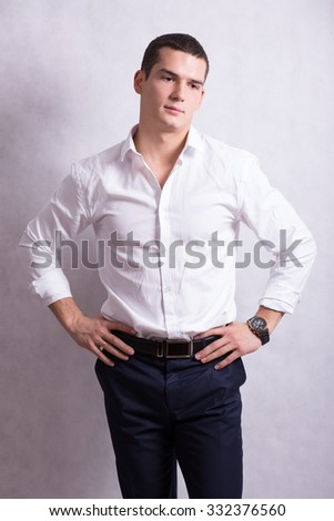 handsome young handsome brunette man in white shirt and black trousers. Business portrait. business style. office. on a white background