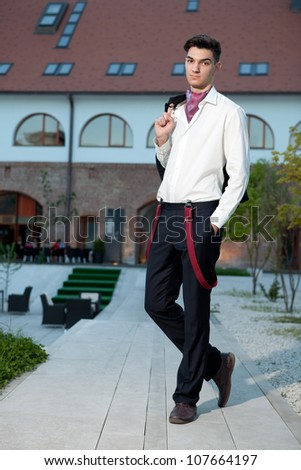Handsome young hipster fashion male model wearing shirt and red braces posing outdoors