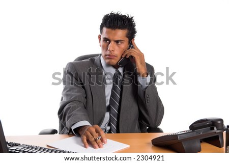 Handsome young Hispanic business man in a grey suit talking on his cell phone and taking notes on a pad of paper