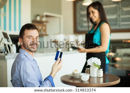 Handsome young Hispanic man holding a credit card after paying for his coffee and cupcake at a cafe and smiling - stock photo