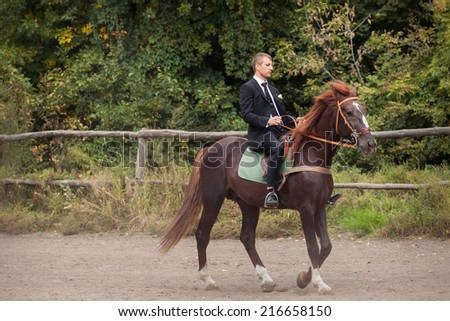 handsome young in black suit groom rides on horse
