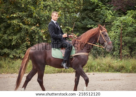 handsome young in black suit groom rides on horse - stock photo