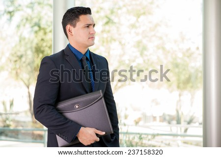 Handsome young lawyer carrying documents in a portfolio and looking towards copy space