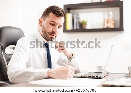 Handsome young lawyer signing some documents and contracts for a client while working in his office