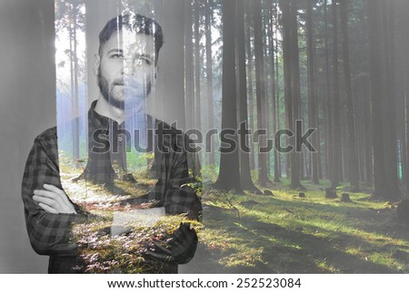 Handsome young lumbersexual man with crossed arms in double exposure with forrest, back to nature concept - stock photo