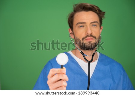 Handsome young male anaesthetist or doctor holding a stethoscope up with the disk facing the camera and the ear pieces in his ears as though he is listening, on a blue background - stock photo