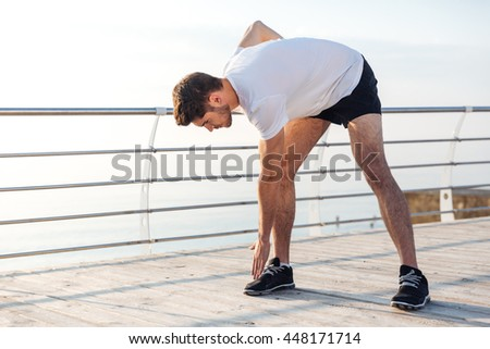 Handsome young male athlete doing morning exercises on wooden terrace - stock photo