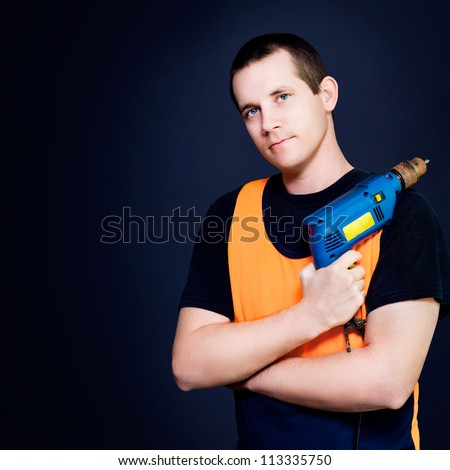 Handsome young male carpenter with power drill in hand standing on a dark studio background with copyspace