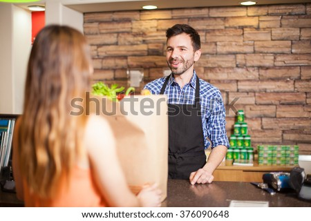 Handsome young male cashier helping a customer at a checkout counter and smiling - stock photo