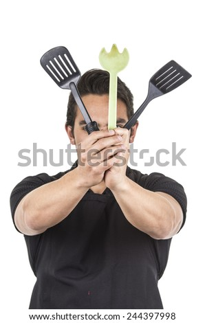 handsome young male chef wearing black apron holding kitchen utensils isolated on white - stock photo