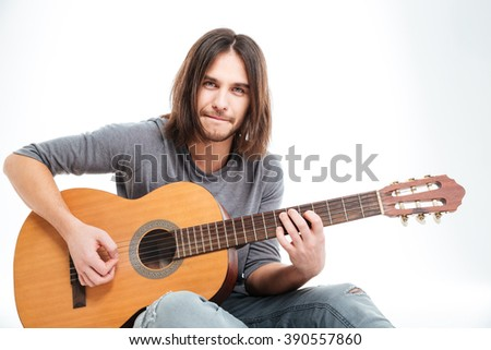 Handsome young male guitarist with long hair sitting and playing acoustic guitar over white background
