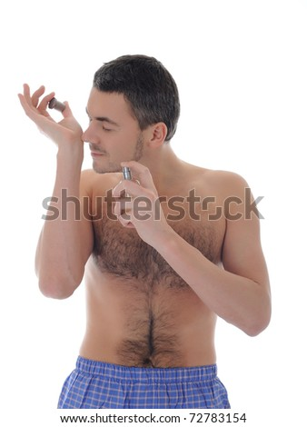 handsome young male spray perfume on his skin. isolated on white background - stock photo