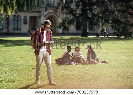 handsome young male student reading book while walking on green grass near university