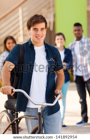 handsome young male teen high school student with a bicycle and friends on background - stock photo