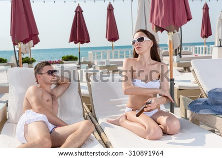Handsome Young Man Admiring his Girlfriend While Sitting on the Lounge Chair and Applying Sunscreen Lotion on her Body on a Sunny Climate in the Resort. - stock photo