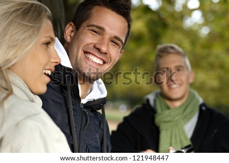 Handsome young man and friends smiling in park, having fun.