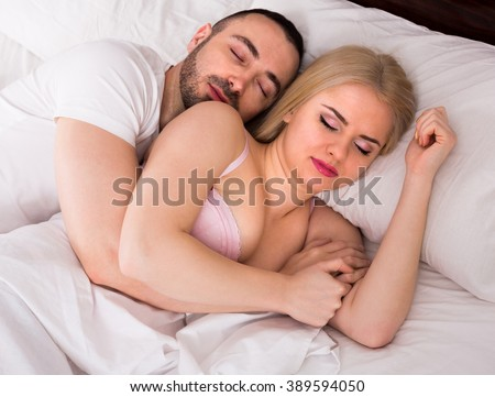 Handsome young man and girlfriend hugging while sleeping
