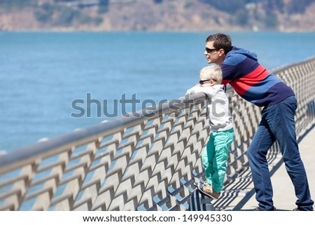handsome young man and his son enjoyng the sea view in san francisco - stock photo