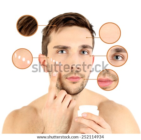 Handsome young man applying cream lotion on face isolated on white - stock photo