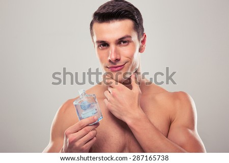 handsome young man applying lotion after shave on face over gray background - stock photo