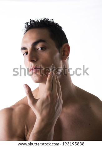 Handsome young man applying moisturizing cream on his face's skin - stock photo