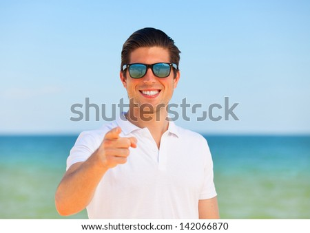 Handsome young man at beach background - stock photo
