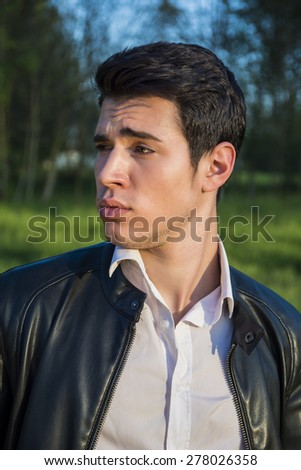 Handsome young man at countryside, in front of field or grassland, wearing white shirt and jacket, looking to left - stock photo