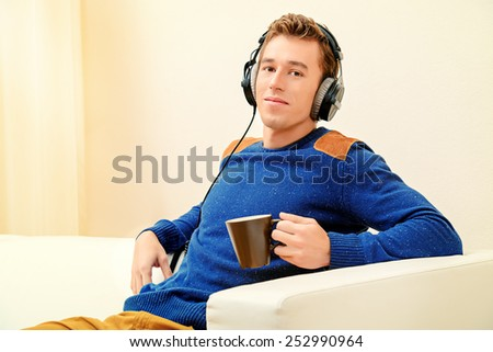Handsome young man at home, listening to music in headphones and smiling. - stock photo