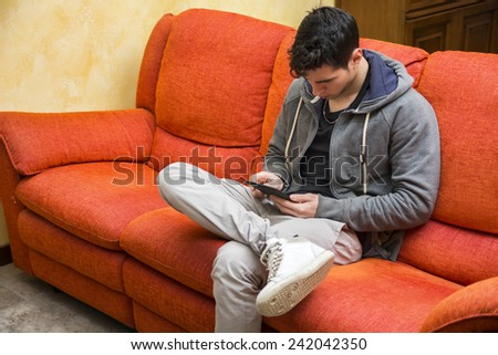 Handsome young man at home reading with ebook reader sitting on a couch - stock photo