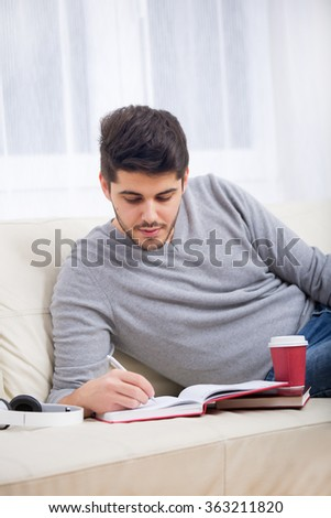 Handsome young man at home writing on notebook, sitting on couch