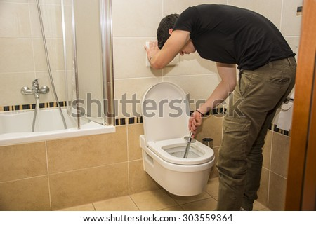 Handsome young man bending down with a brush in his hand cleaning the bathroom lavatory, wiping the ceramic latrine - stock photo