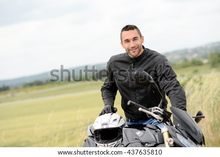 handsome young man biker with white helmet riding black motorcycle