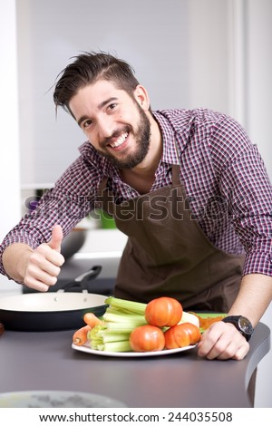 Handsome young man chopping vegetables - stock photo