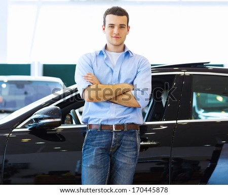 Handsome young man consultant at car salon standing near car - stock photo