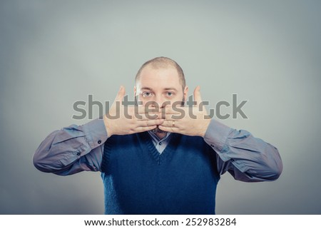 Handsome young man covering his mouth with hand, not laughing or in silence - stock photo