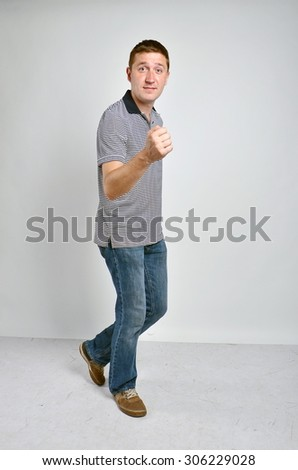 Handsome young man dancing, full length portrait, grey background
