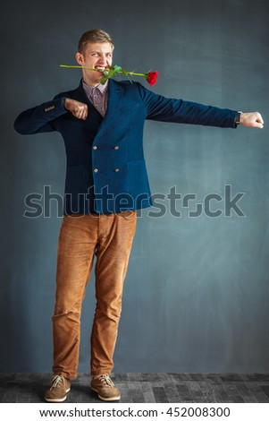 Handsome young man dancing with a red rose in his mouth against grey wall background - stock photo