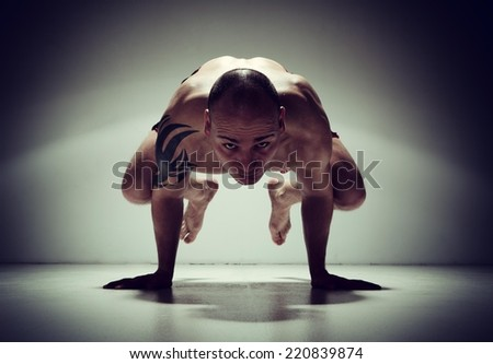 Handsome young man doing crow yoga pose in dark. Light on a boom stand used. - stock photo