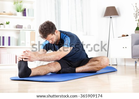 Handsome Young Man Doing Hamstring Stretch Exercise on Top of a Mat at Home. - stock photo