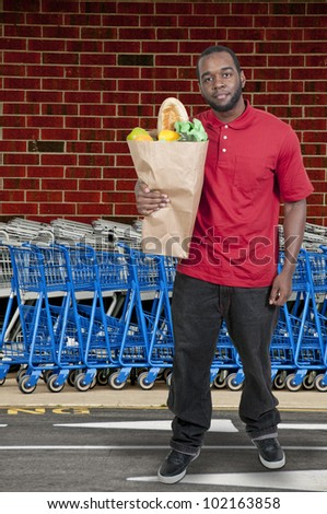 Handsome young man doing his grocery shopping
