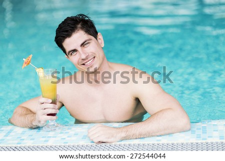 Handsome young man drinking a cocktail while relaxing in a swimming pool - stock photo