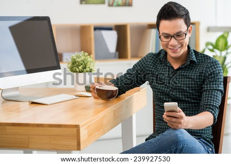 Handsome young man drinking coffee and reading a message on his smartphone - stock photo