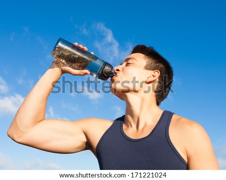Handsome young man drinking water - stock photo