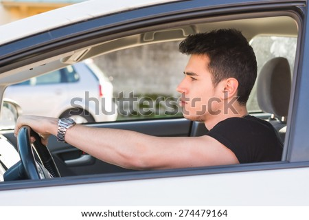Handsome Young Man Driving a Car, wearing black t-shirt, hand on wheel - stock photo