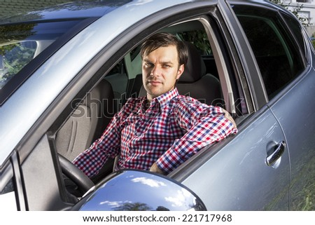 Handsome young man driving his new car  - stock photo