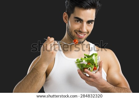 Handsome young man eating a healthy salad, isolated over a gray background - stock photo