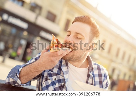 Handsome young man eating a slice of pizza outside on the street - stock photo