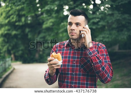 Handsome young man eating sandwich autdoor. He is holding a phone