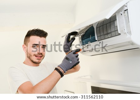 handsome young man electrician installing air conditioning in a client house  - stock photo
