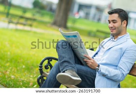 Handsome young man enjoying and reading newspapers, outdoor - outside